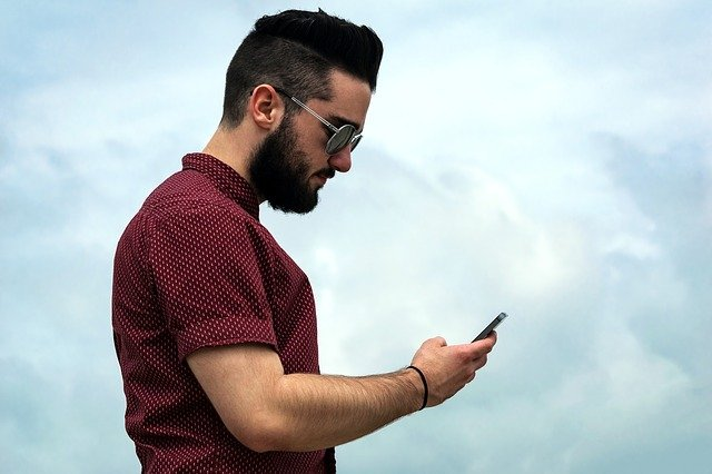muž s mobilem a brýlemi