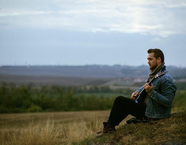 muž na stráni hrající na kytaru